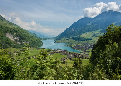 Aerial view of beautiful emerald green water alpine lake and village in summer landscape of alps in Switzerland