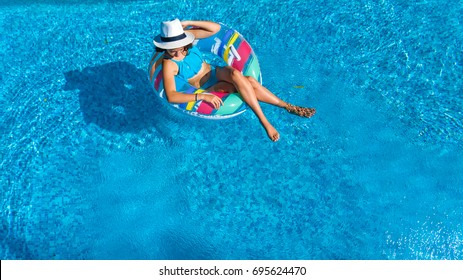 Aerial view of beautiful girl in swimming pool from above, relax swim on inflatable ring donut and has fun in water on family vacation