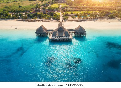 Aerial view of beautiful hotel in Indian ocean at sunset in summer. Zanzibar, Africa. Top view. Landscape with wooden hotel on the  sea, blue water, sandy beach, green trees, buildings. Luxury resort