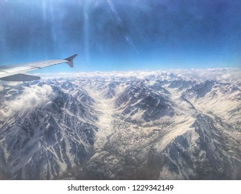 Aerial view of the beautiful intricate and snow-capped mountains with wing tip of the plane On the way to Islamabad to Skardu.scenery of the mountains from the plane window.