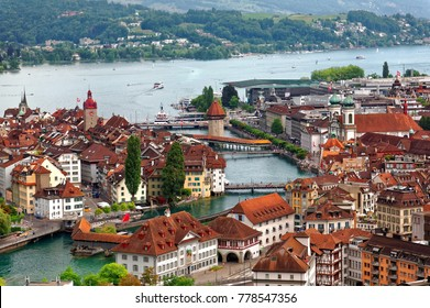 Aerial view of beautiful Lucerne City by lakeside with wooden Chapel Bridge ( Kapellbrucke ) over Reuss River, beautiful houses in old town & tourists boats cruising on the lake, in Switzerland Europe
