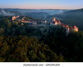 Aerial view of beautiful, Moravian royal castle Veveri or Burg Eichhorn, standing on a rock above water dam on river Svratka. Large castle above misty trees in early morning light. Aerial photography.