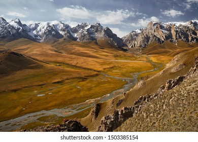 Aerial view of beautiful mountain valley with river and snow peaks near Kel Suu Lake in Naryn region, Kyrgyzstan