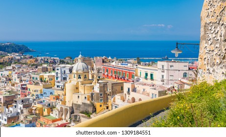 Aerial view of beautiful Procida in sunny summer day. Colorful houses, cafes and restaurants in Marina Corricella, clear blue sky and sea in Procida Island, Italy.