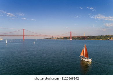 Aerial view of a beautiful sail boat on the Tagus River with the 25 of April Bridge on the background, in the city of Lisbon, Portugal