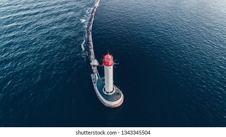 Aerial view of the beautiful snow-white lighthouse with a contrasting red roof against the blue water of the black sea, Odessa, Ukraine