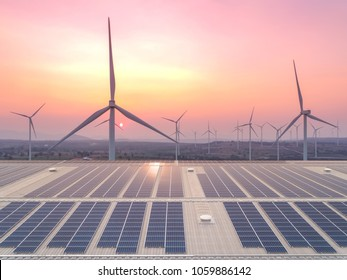 Aerial view of beautiful sunrise above the solar cell panel on the rooftop of factory building with wind turbine electrical power as futuristic on sustainability and innovation concept