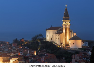 Aerial view of beautiful town Piran in Istria, Slovenia, at dusk. Church of Saint George with its bell tower illuminated on the right.