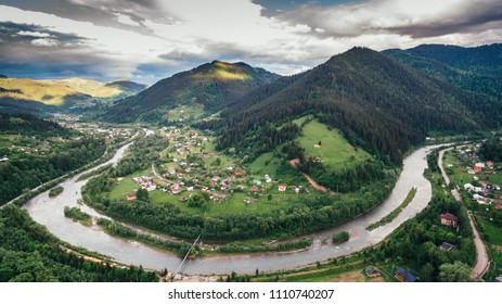 Aerial View: Beautiful ] village located along the riverin the middle of the mountains. The landscape of Carpathians