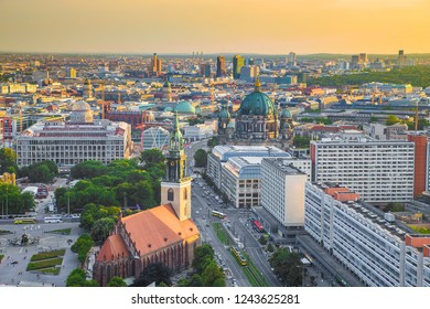 Aerial view of Berlin skyline with Marienkirche and famous Berlin Cathedral in beautiful golden evening light with clouds at sunset, central Berlin, Germany