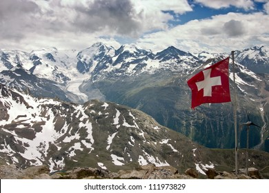 Aerial View of Bernina Mountain Range in Summer with Swiss Flag in Foreground