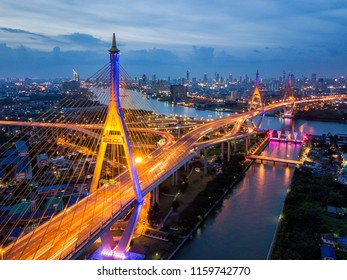 Aerial view of Bhumibol suspension bridge cross over Chao Phraya River in Bangkok city with car on the bridge at sunset sky and clouds in Bangkok Thailand.