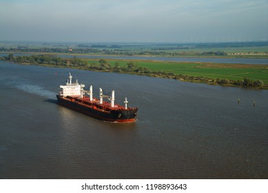 aerial view of a big freight ship on the river Weser, Germany in front of Europe's biggest river island Harriersand at a sunny but a bit misty day
