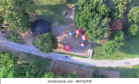 Aerial view of a big kid games playground at Bellaire Park in Houston, Texas. Elevated view of slides, swings in the park surrounded by green trees. Children outdoor play, recreation concept. Panorama
