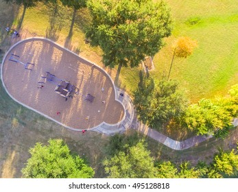 Aerial view a big kid games playground at Harwin Park in Houston, Texas in fall. Elevated view of slides and swings in the park surrounded by green trees. Children outdoor play and recreation concept.