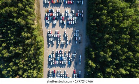 Aerial view of big parking lot of new cars. Automobile factory. New car factory awaiting transport from the port. Top down view.