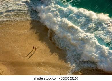 Aerial view of big waves and turquoise blue ocean in Nusa Penida, Bali, Indonesia.  Waves and beach in Kelingking Beach, Nusa Penida.