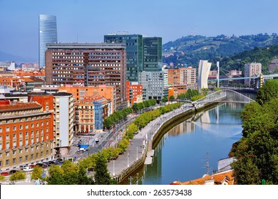 Aerial view of Bilbao, Spain city downtown with a Nevion River, Zubizuri Bridge and promenade. Mountain at the background, clear blue sky.