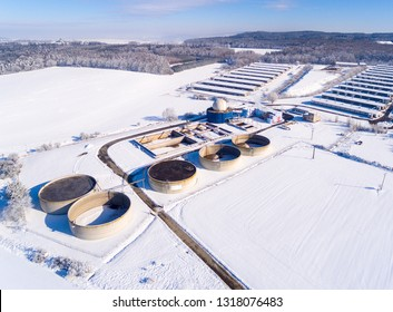 Aerial view to biogas plant from pig farm in snowy fields. Renewable energy from biomass. Winter on countryside. Modern agriculture in European Union.