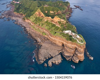 Aerial view of Bitoujiao lighthouse - Famous scenery of Taiwan northeast corner, birds eye view use the drone at sunrise, shot in Bitoujiao cape, Ruifang district, New Taipei, Taiwan.