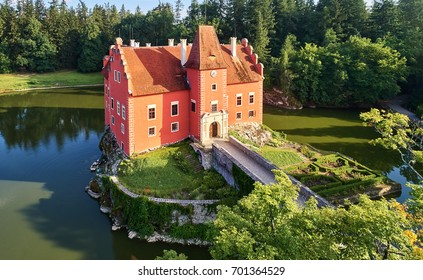 Aerial view of bizarre water castle Cervena Lhota,  picturesque renaissance-style red château standing at the middle of a lake on a rocky island, south Bohemia, Czech Republic. Touristic destination.