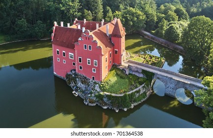 Aerial view of bizarre water castle Cervena Lhota,  picturesque renaissance-style red château standing at the middle of a lake on a rocky island in the czech landscape, south Bohemia, Czech Republic.