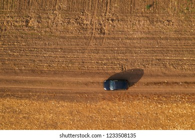 Aerial view of black car on dirt road through countryside, top view of off-road driving vehicle from drone pov
