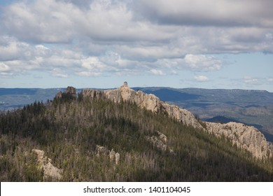 An aerial view of Black Elk Peak ( formerly Harney Peak) and tower which overlooks eroded rock formations and a forest in Custer State Park, South Dakota.