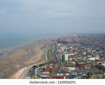 aerial view of blackpool looking south showing the beach at low tide with the roads and buildings of the town stretching down the coast to the irish sea on the horizon