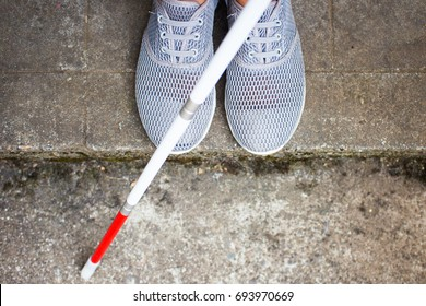 Aerial View of Blind Person's Shoes and a Long White Cane Near a Curb