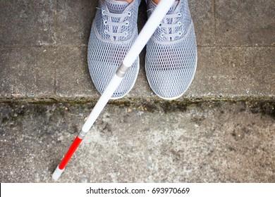 Vista aérea de sapatos de pessoa cega e uma longa bengala branca perto de um meio-fio