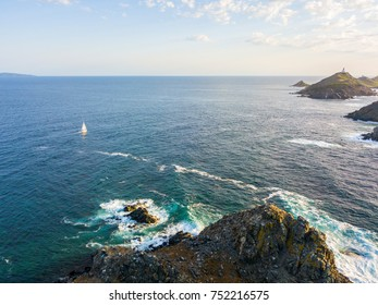 Aerial view of the Bloods Islands and Lighthouse, Corsica, France: rocks, waves and sailboat. Four islands of dark red porphyry, small archipelago in the Gulf of Ajaccio. Sunset