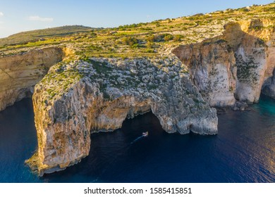 Aerial view of Blue grotto and boat, cliffs. Blue clear sky, winter, rocks. Malta island