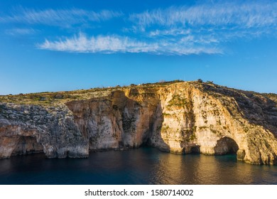 Aerial view of Blue grotto, cliffs. Blue clear sky with clouds, winter, rocks. Malta