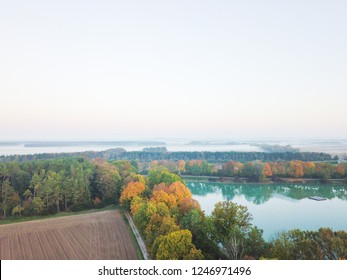Aerial view of blue lake in autumn forest with misty fields in the background