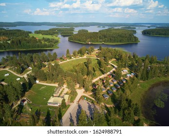 Aerial view of blue lake and green forests on a sunny summer day above a caravan camping site. Bird's eye view drone photography. Ruovesi, Finland.