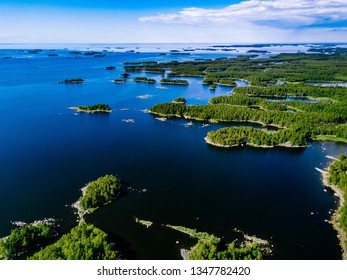 Aerial view of blue lakes and green forests on a sunny summer day in rural Finland. Drone photography from above