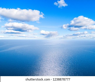 Aerial view of a blue sea water background and sun reflections. Aerial flying drone view. Waves water surface texture on sunny tropical ocean. Aerial photography. Birdseye. Sea, beach, sky, clouds.