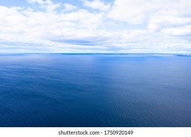 Aerial view of a blue sea water background and sun reflections. Aerial flying drone view. Waves water surface texture on sunny tropical ocean. Aerial photography. Birdseye.