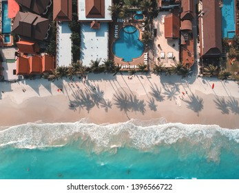 Aerial view of blue sea waves crushing against the sandy coast line, people enjoy summer near resorts and hotel line