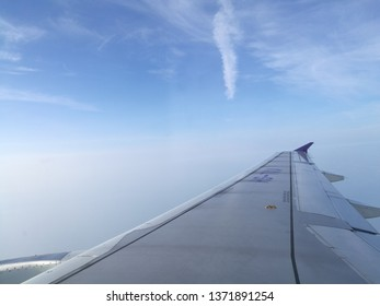 Aerial view of blue sky and cloud seen through window of an aircraft, airplane wing from window.