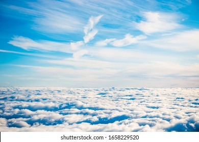 Aerial view of blue sky with layers of white fluffy cumulus and cirrus clouds