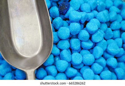 aerial view of blue sugar candies with a metallic shovel
