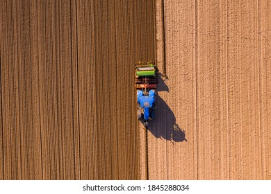Aerial view of a blue tractor plowing a field, leaving marks on the field