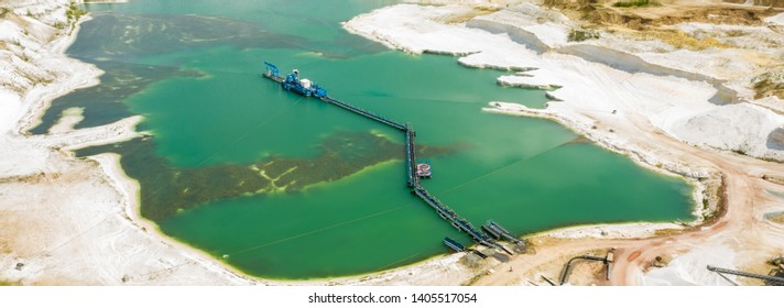 Aerial view of a blue-green quarry pond for quartz sand in Germany with the suction dredger and the conveyor belt for the sand
