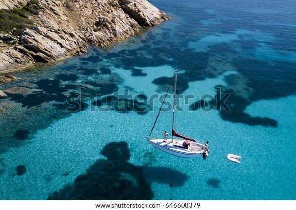 Luftbild eines Schiffes vor der Insel Mortorio auf Sardinien. Der Strand mit türkisfarbenem und transparentem Meer. Emerald Coast, Sardinien, Italien.