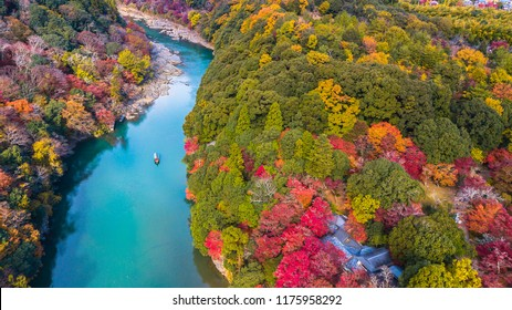 Aerial view boat on the river bring tourist people to enjoy autumn colors along katsura river to Arashiyama mountain area during fall season in Arashiyama, Kyoto, Japan.