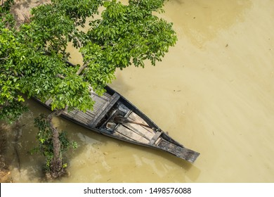 An aerial view of a boat with a paddle in the prow for transport in a flooded area of rural Asia.