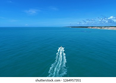 Aerial view of boat sailing in the paradise sea with clear water. Fantastic landscape. Great beach view. Arraia d'Ajuda, Bahia, Brazil