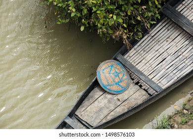 An aerial view of a boat for transport in a flooded area of rural Asia with a boatman's bamboo hat in the prow